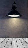 倒空有灯罩的木透视平台从垂悬现代黑金属的灯在与Copyspace的灰色墙壁背景使用了 库存图片