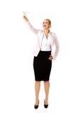 Молодая усмехаясь бизнес-леди указывая для copyspace или что-то Стоковое Фото