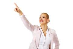 Молодая усмехаясь бизнес-леди указывая для copyspace или что-то Стоковые Изображения