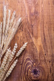 Copyspace background eras of wheat on old wooden Royalty Free Stock Photography