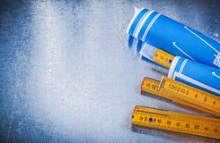 Copyspace del metro di legno blu dei disegni di costruzione su metallico Immagine Stock