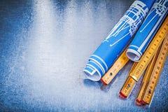 Copyspace del metro di legno blu dei disegni di ingegneria su metallico Fotografia Stock Libera da Diritti