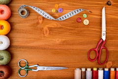 Copyspace frame with sewing tools and accesories on wooden background Royalty Free Stock Images