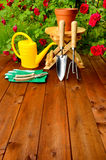 Copyspace gardening tools on wooden table and rose flowers background Royalty Free Stock Image