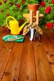 Copyspace Gartenarbeitwerkzeuge auf Holztisch und rosafarbenem Blumenhintergrund Lizenzfreies Stockbild