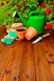 Copyspace Gartenarbeitwerkzeuge auf Holztisch und rosafarbenem Blumenhintergrund Stockbild