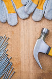 Copyspace image claw hammer nails protective gloves on wooden bo Stock Images