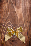 Copyspace image golden christmas bow with small bell on old wood Royalty Free Stock Photos