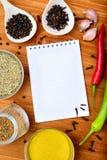Copyspace-Lebensmittelrahmen mit Notizblockpapiergewürzen und kochen Zubehör Stockfotografie