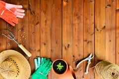 Copyspace-Rahmen mit Gartenarbeitwerkzeugen und -gegenständen auf altem hölzernem Hintergrund Lizenzfreies Stockbild