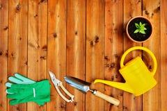 Copyspace-Rahmen mit Gartenarbeitwerkzeugen und -gegenständen auf altem hölzernem Hintergrund Lizenzfreie Stockfotos
