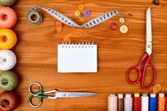 Copyspace-Rahmen mit nähenden Werkzeugen und Zubehör auf hölzernem Hintergrund Stockfotos