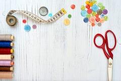 Copyspace-Rahmen mit nähenden Werkzeugen und Zubehör auf weißem hölzernem Hintergrund Stockbild