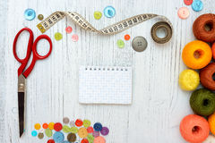 Copyspace-Rahmen mit nähenden Werkzeugen und Zubehör auf weißem hölzernem Hintergrund Lizenzfreie Stockbilder