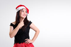 Copyspace: what to shop on Christmas. Beautiful Christmas girl posing against white background, seems attracted to something on her side, copy space ready to use Stock Photos