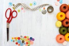 Copyspacekader met het naaien van hulpmiddelen en toebehoren op witte houten achtergrond Stock Afbeeldingen