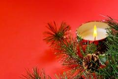 Copyspacekort för nytt år Julgrangranfilial, bränningstearinljus, garneringar, på röd bakgrund royaltyfri bild
