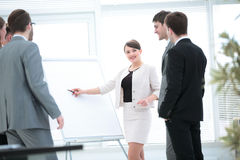 Copywriter and designers stand next to a blank poster and discus Royalty Free Stock Photos