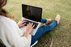 Copywriter. Female copywriter working on laptop in the park, view over the shoulder Royalty Free Stock Photography