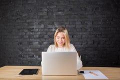 Copywriter grazioso della donna che lavora in Internet sul NET-libro portatile, sedentesi nell'ufficio Fotografie Stock
