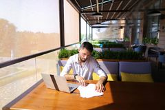 Copywriter typing text on laptop at cafe table. Copywriter typing article from papers on laptop keyboard and hurrying. Hardworking dressed in black shirt looks Royalty Free Stock Images