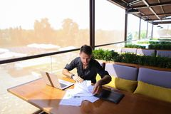 Copywriter typing text on laptop at cafe table. Copywriter typing article from papers on laptop keyboard and hurrying. Hardworking dressed in black shirt looks Royalty Free Stock Photo