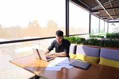 Copywriter typing text on laptop at cafe table. Copywriter typing article from papers on laptop keyboard and hurrying. Hardworking dressed in black shirt looks Stock Photo