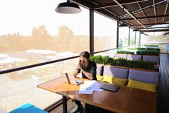 Copywriter typing text on laptop at cafe table. Copywriter typing article from papers on laptop keyboard and hurrying. Hardworking dressed in black shirt looks Stock Images