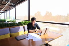 Copywriter typing text on laptop at cafe table. Copywriter typing article from papers on laptop keyboard and hurrying. Hardworking dressed in black shirt looks Stock Photos