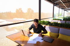 Copywriter typing text on laptop at cafe table. Copywriter typing article from papers on laptop keyboard and hurrying. Hardworking dressed in black shirt looks Stock Image