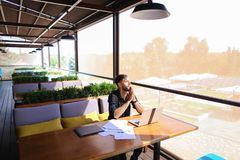 Copywriter typing text on laptop at cafe table. Copywriter typing article from papers on laptop keyboard and hurrying. Hardworking dressed in black shirt looks Royalty Free Stock Photography