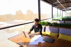 Copywriter typing text on laptop at cafe table. Copywriter typing article from papers on laptop keyboard and hurrying. Hardworking dressed in black shirt looks Royalty Free Stock Photos