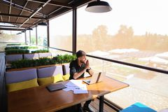 Copywriter typing text on laptop at cafe table. Copywriter typing article from papers on laptop keyboard and hurrying. Hardworking dressed in black shirt looks Stock Photography