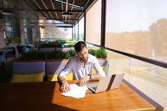 Copywriter typing text on laptop at cafe table. Copywriter typing article from papers on laptop keyboard and hurrying. Hardworking dressed in black shirt looks Royalty Free Stock Image