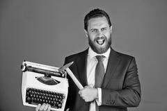 Copywriting błędy biznesowy mężczyzna, agresywny biznesmen z maszyna do pisania i młot, obrazy royalty free