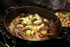 Coq au vin. Traditional French chicken casserole, coq au vin. Button mushrooms, bacon, shallots, thyme and a red wine sauce in a big black casserole pan Stock Photo