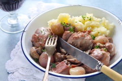 Coq au Vin. In old enamel bowl, with lacy napkin and vintage cutlery.  Traditional French chicken casserole, with mashed potato Stock Image