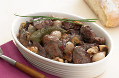 Coq au vin. With pearl onion, mushrooms and bay leaf in oval bowl Stock Images