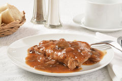 Coq Au Vin. A plate of Coq Au Vin with a basket of dinner rolls Stock Photo