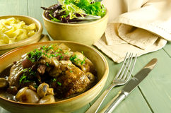Coq au vin with salad and noodles. Classic French cuisine, coq au vin Royalty Free Stock Photo