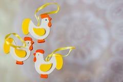 Coq en bois coloré de décor de Pâques, sur le fond blanc du napperon blanc de dentelle Décorations de fête Avec l'endroit pour le Photos stock