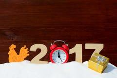 Coq et les numéros 2017 dans une congère sur un fond en bois Images stock