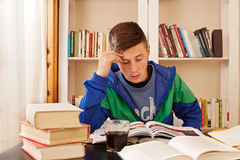 Coque de consumición del adolescente masculino mientras que estudia Fotos de archivo