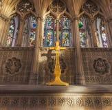 COQUE, R-U - 3 MARS 2019 : Un crucifix peint jaune se repose devant le verre souillé dans la coque Minster photographie stock