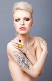 Coquete que olha a mulher loura com estúdio da tatuagem e isolat vermelho dos bordos Foto de Stock Royalty Free
