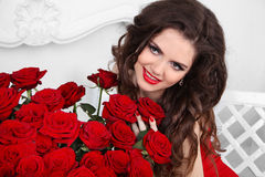 Coquette Girl. Beautiful happy woman with bouquet of many red ro Stock Photos