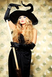 Coquette witch. Charming halloween witch with broom over vintage background Royalty Free Stock Photo