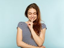 Coquettish attractive girl secret finger on lips. Coquettish attractive flirty young girl has a secret. young beautiful woman portrait on blue background. finger stock photo