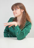 Coquettish beautiful girl sits at table Stock Image