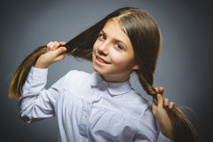 Coquettish girl. Closeup Portrait handsome teen smiling isolated on grey stock image
